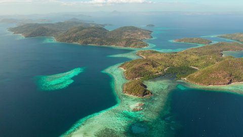 aerial view tropical islands with blue lagoon, coral reef and sandy beach. Palawan, Philippines. Islands of the Malayan archipelago with turquoise lagoons.