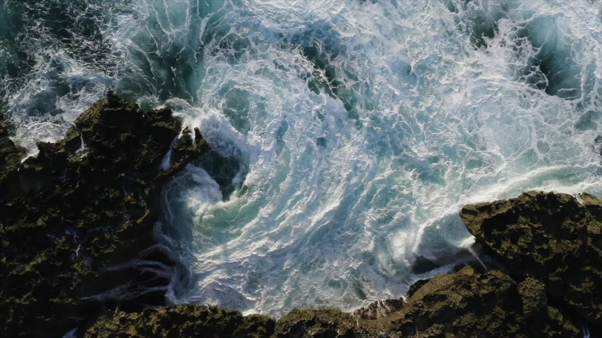 Breathtaking top aerial slow motion view of azure ocean and giant waves crashing at rocky cliff with splashing and white foam. Bali island, Indonesia