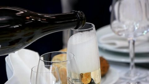 The waiter pours champagne into a glass. The waiter pours a glass of white wine.