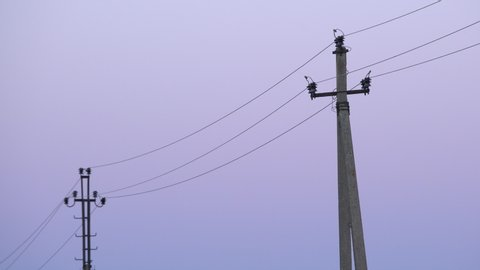 Old concrete electricity poles in the village at twilight. Rustic phone poles with high voltage cables and colourful dawn sky background