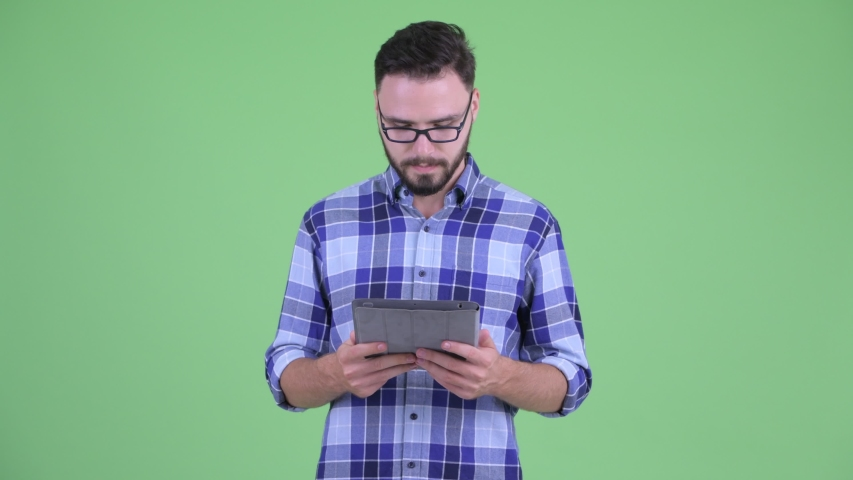 Happy young bearded hipster man thinking while using digital tablet | Shutterstock HD Video #1035606908