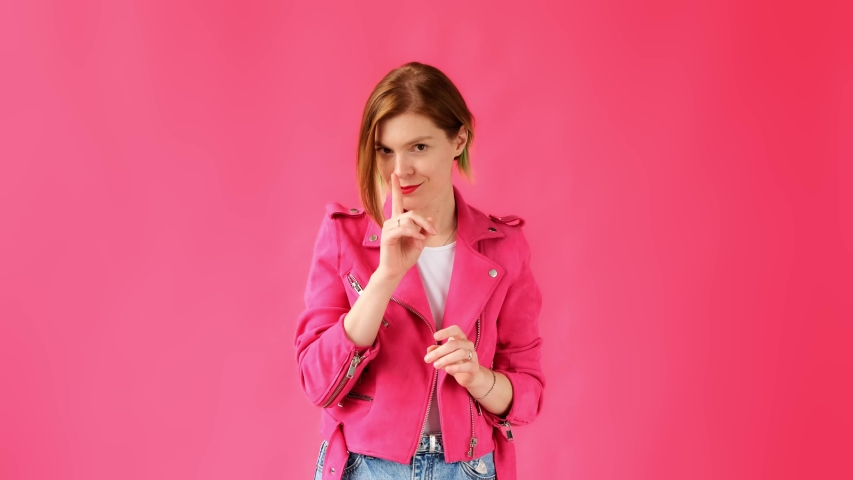 Secret. Quiet. A woman on a pink background in pink clothes looks around and holds a finger to her lips showing a sign of silence and secret.  | Shutterstock HD Video #1035632198