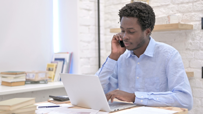 Working African Man talking on Phone | Shutterstock HD Video #1035670358