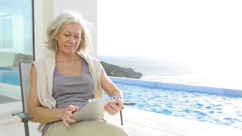 Senior woman sitting by a pool with electronic tab