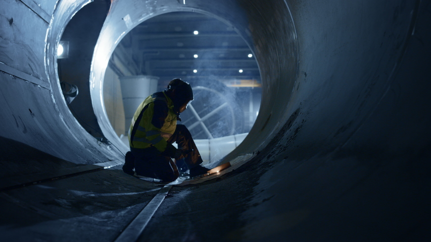 Professional Heavy Industry Welder Working Inside Pipe, Wears Helmet and Starts Welding. Construction of the Oil, Natural Gas and Fuels Transport Pipeline. Industrial Manufacturing Factory | Shutterstock HD Video #1035704198