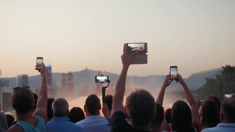 BARCELONA, SPAIN - JULY 2019: Crowd taking pictures with cell phones, fountains in barcelona, event. A crowd taking pictures with cell phones at an outdoor event