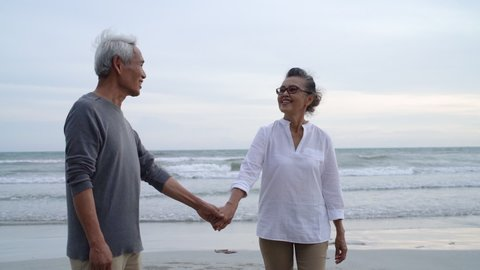Asian couple senior elder retire resting relax holding hand walking at sunset beach honeymoon family together happiness people lifestyle, Slow motion footage