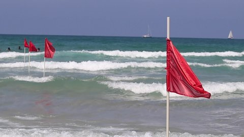 Red flag on sand beach for warning of dangerous of swimming in the sea, Israel. Mediterranean sea