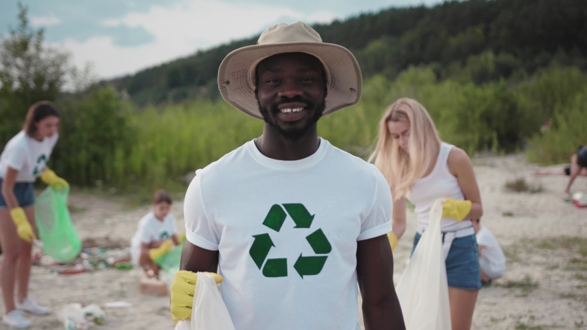 Modern ecology movement. Portrait of smiling afro-american handsome student picking up rubbish into plastic bag. Team of vigorous volunteers in eco T-shirts cleaning down the lake beach. | Shutterstock HD Video #1035821528