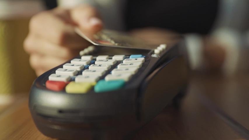 Close-up of woman rotating credit card in hands applying on pos reader for checkout and wireless money transaction. Credit card payment. Outdoor view. | Shutterstock HD Video #1035891428