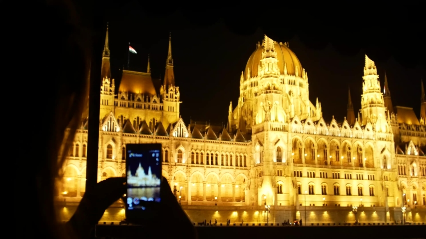 Night telephoto shot of Hungarian parliament building, girl photographing Budapest night parliament | Shutterstock HD Video #1035910328