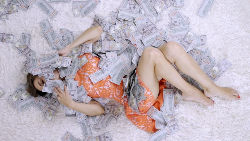 Girl lies on a white bed in lot of money. The girl enjoys lot of money. slow motion. Huge wealth of money. | Shutterstock HD Video #1035984158
