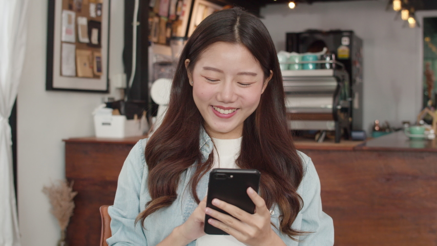 Freelance Asian women using mobile phone at cafe. Young Japanese Asian girl using smartphone checking social media on the internet on the table at coffee shop concept. | Shutterstock HD Video #1035988178