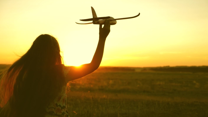 Happy girl runs with a toy airplane on a field in the sunset light. children play toy airplane. teenager dreams of flying and becoming a pilot. girl wants to become a pilot and astronaut. Slow motion