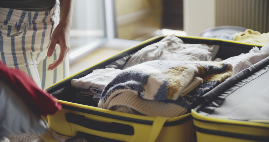 Coseup of woman packing a luggage on bed