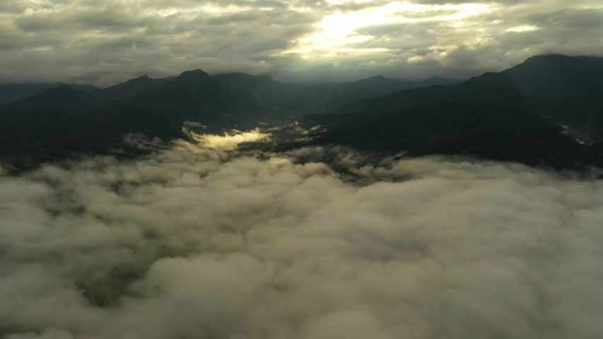 Aerial view flying in the clouds when the sunrise on the mountain | Shutterstock HD Video #1036060448