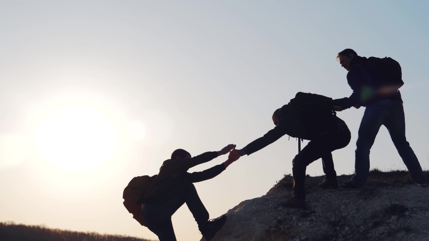 At sunset, tourists climb the mountain, overcoming obstacles. Silhouettes of men helping each other in a difficult situation. A friend, a young man, gives a helping hand. #1036173428