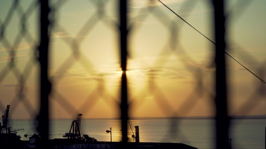 Lisbon harbor sunrise with cranes silhouette through out of focus wire fences | Shutterstock HD Video #1036260668