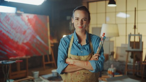 Portrait of Talented Young Female Artist Dirty with Paint, Wearing Apron, Crosses Arms while Holding Brushes, Looks at the Camera with a Smile. Authentic Creative Studio with Large Canvas and Tools