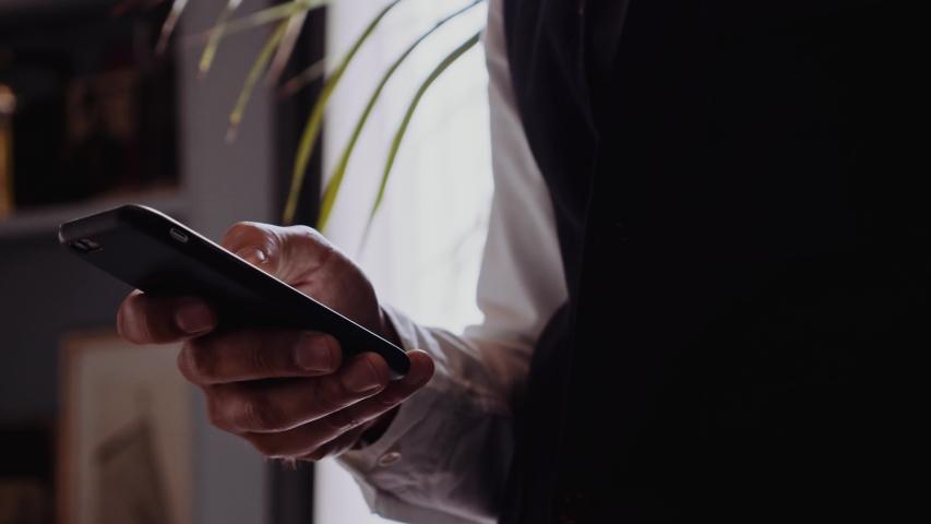 Businessman checking mobile phone standing in the office | Shutterstock HD Video #1036342928