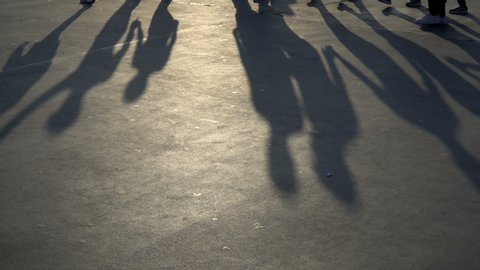 Shadows of folk dancers at the sunset time