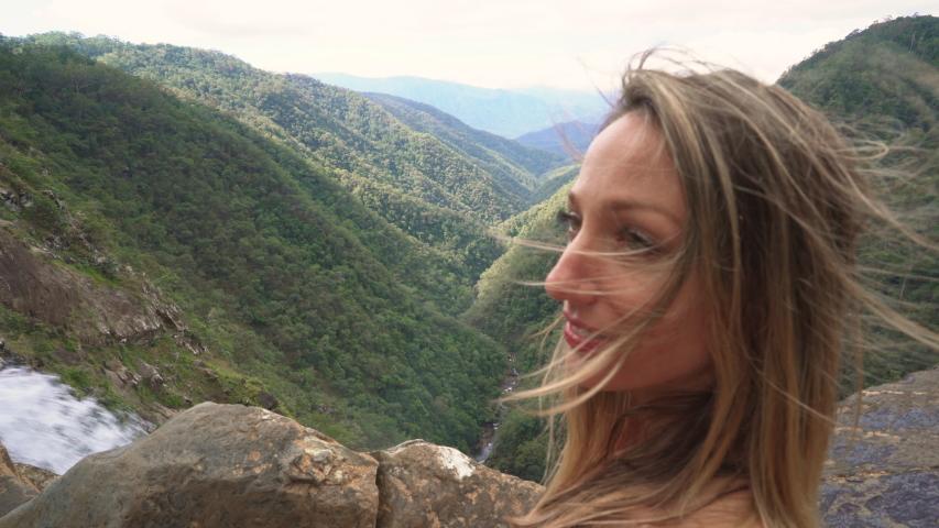 A tourist girl enjoy the amazing views from  an incredible waterfall. Filmed at Windin Falls Queensland. Australia. | Shutterstock HD Video #1036465808