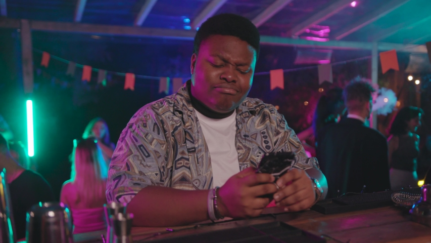 Handsome sexy african american boy smiling using smartphone shaking head into cool club party music enjoying sound closing eyes sitting on bar. | Shutterstock HD Video #1036481558