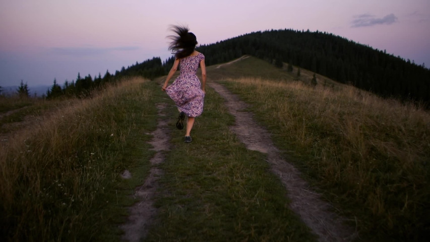 Camera follows hipster millennial young woman in a long dress developing in the wind running up on top of mountain summit at sunset, raises arms into air, happy and drunk on life, youth and happiness | Shutterstock HD Video #1036583678