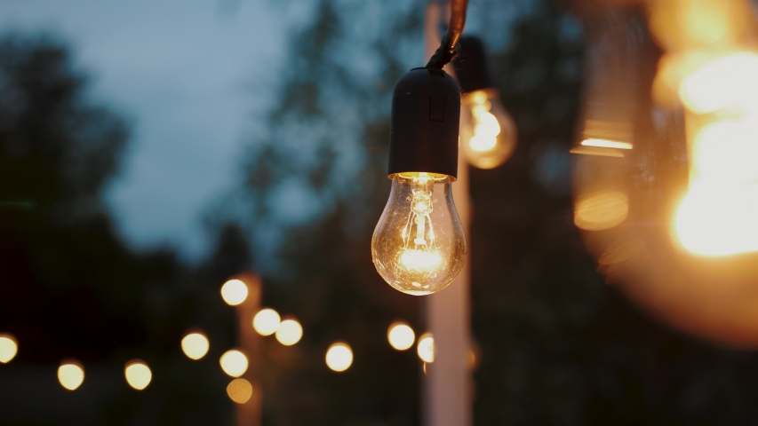 Festival decorative string lights hang and glow outdoors at night. Warm lighting, vintage garland of lamps or glass lantern, electric bulbs shining, decoration for holiday.