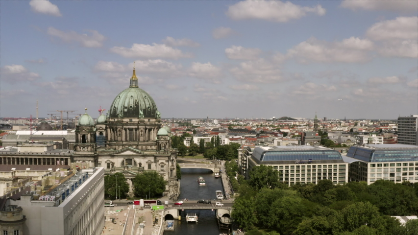 The Berlin cathedral in an aerial flight. The drone is flying slowly to the Berliner Dom on a sunny day. The cityscape of Berlin, Germany with its busy streets and bridges across the river Spree. | Shutterstock HD Video #1036960418