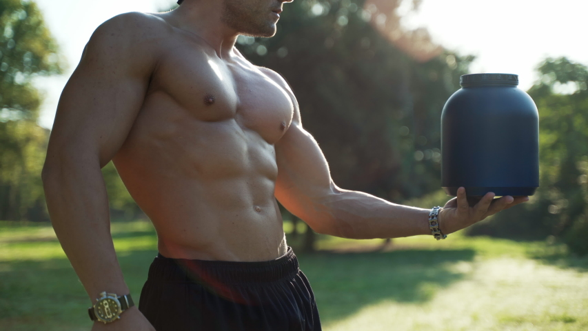 Handsome shirtless bodybuilder with perfect muscular torso holding a bottle of nutritional supplements for sportsmen. Strong athlete recommending sportive food additives during hard training. Protein   Shutterstock HD Video #1036992638