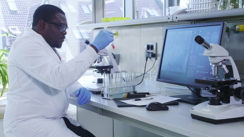 African-american scientist working in lab. Doctor making microbiology research. Biotechnology, chemistry, bacteriology, virology, dna and health care. | Shutterstock HD Video #1037004698