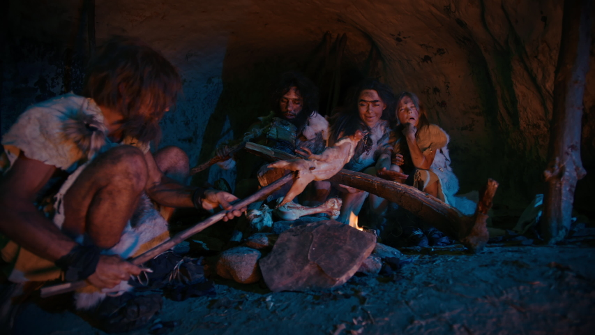 Neanderthal or Homo Sapiens Family Cooking Animal Meat over Bonfire and then Eating it. Tribe of Prehistoric Hunter-Gatherers Wearing Animal Skins Eating in a Dark Scary Cave at Night. Zoom in Shot | Shutterstock HD Video #1037018318