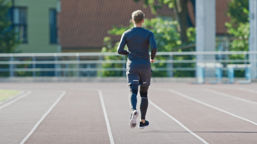 Smiling Athletic Fit Man in Grey Shirt and Shorts Jogging in the Stadium. He is Running Fast on a Warm Summer Afternoon. Athlete Doing His Routine Sports Practice. Slow Motion Shot. | Shutterstock HD Video #1037027258