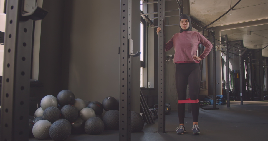 Closeup portrait of young attractive athletic muslim female in hijab doing leg resistance training in gym indoors | Shutterstock HD Video #1037069138