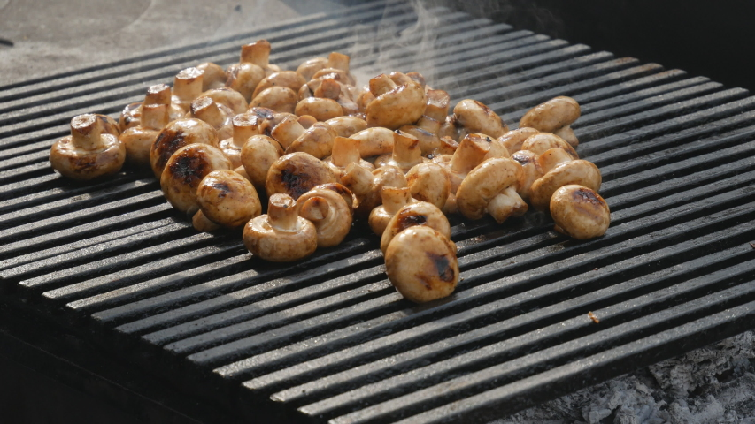 Chef's hands cooks mushrooms on the grill. Delicious, wholesome grilled food. Diet vegan barbecue. barbecue party | Shutterstock HD Video #1037174558