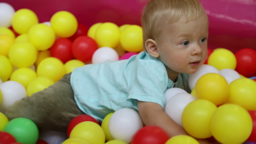 Baby boy in the pool with balls in the children's entertainment center. Slow motion | Shutterstock HD Video #1037177048