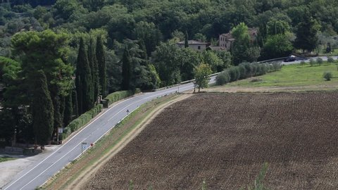 Greve in Chianti, Tuscany, Italy. Road with cars on the Chianti hills. Cultivated fields and farmhouses in the Tuscan countryside near Florence.