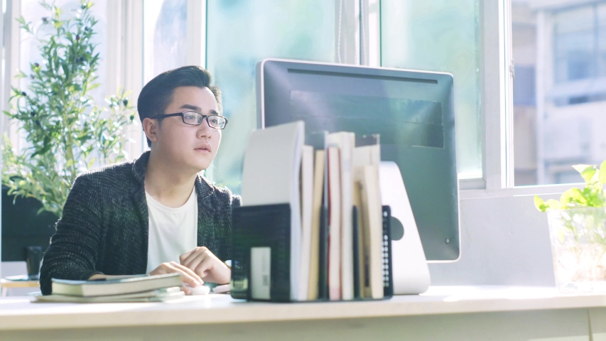 Young asian business man sitting at desk working on desktop computer | Shutterstock HD Video #1037186888