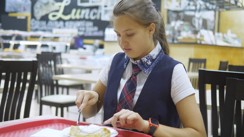 Girl teenager having lunch in the school cafeteria. | Shutterstock HD Video #1037198768