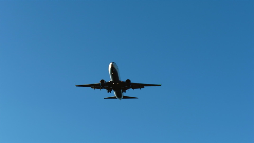 Plane flies in a blue sky with clouds overhead, preparing to land at the airport at sunset or sunrise. | Shutterstock HD Video #1037222648