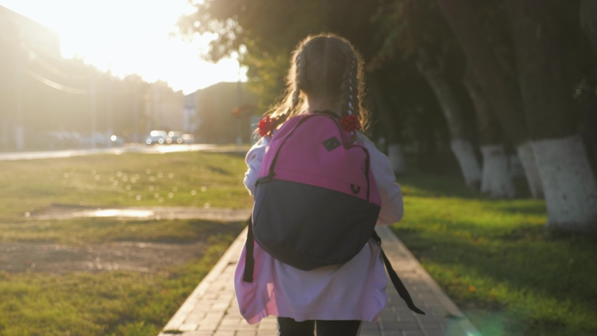 Little girl with a backpack run to school. School and kindergarten education concept. Back view, slow motion and steadicam video. | Shutterstock HD Video #1037262158