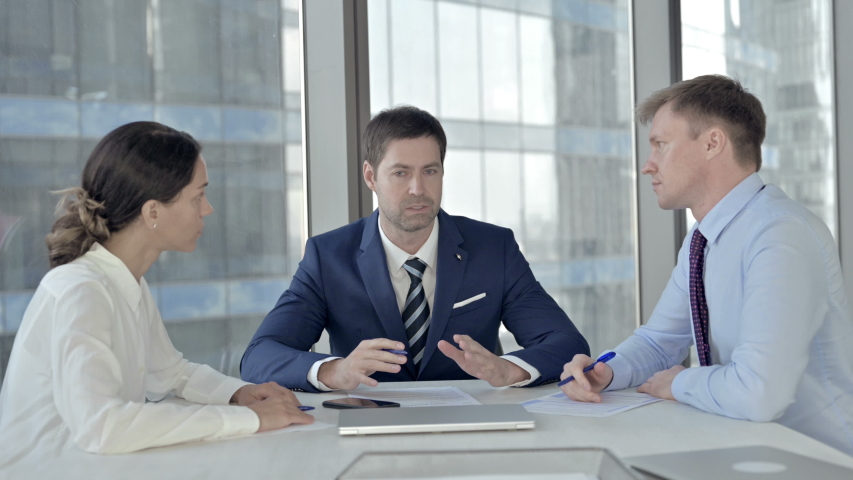Middle Aged Businessman having Reading Documents with his Assistants in Boardroom | Shutterstock HD Video #1037296388
