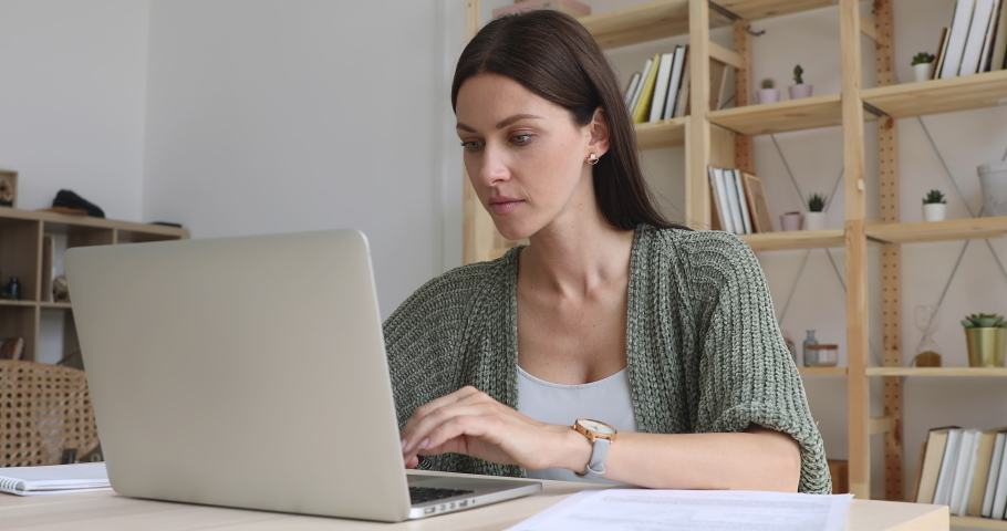 Focused businesswoman doing paperwork working online on laptop sit at home office desk, female entrepreneur professional freelancer using computer software pay bills in app typing at modern workplace | Shutterstock HD Video #1037298248