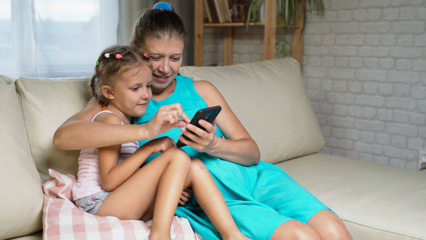 Little Girl Child With Mother Home On Sofa Using Smartphone   Shutterstock HD Video #1037314508