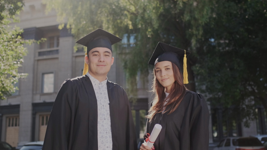 Just graduated multinational excited and happy people. Adult man and girl standing in mantle with academic cap and makes YES gesture joyfully. University degree in modern higher knowledge institute. | Shutterstock HD Video #1037346878