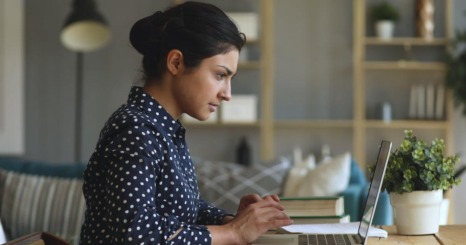 Focused young indian woman college university student doing homework assignment using laptop computer typing studying e learning on pc technology sit at home desk, distance online education concept | Shutterstock HD Video #1037352938