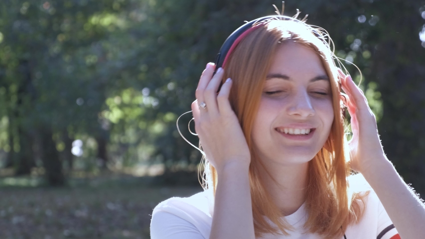 Pretty teenage girl with red hair listening to music in earphones outdoors in summer park.   Shutterstock HD Video #1037355398