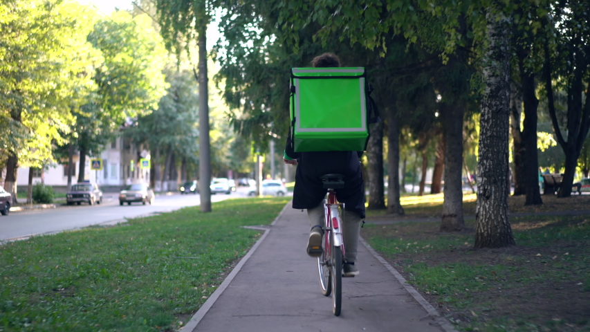 Delivery man with green backpack rides a bicycle through the city with food delivery.   Shutterstock HD Video #1037410598