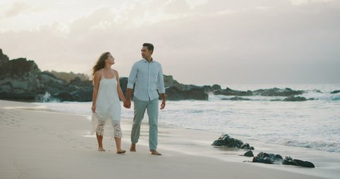 Happy mixed race couple walking together on the beach at sunset